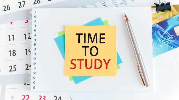 黄色い紙の正方形に書かれた追加の勉強の時間。白いデスクトップ上のクレジットカード、ペン、文房具。ビジネス、金融、教育の概念。セレクティブフォーカス。