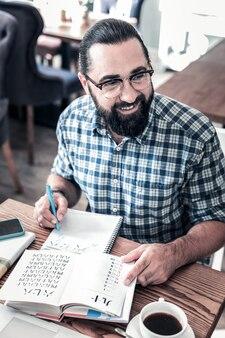 勉強する時間。外国語を勉強することに興奮している眼鏡をかけている陽気なひげを生やしたビジネス