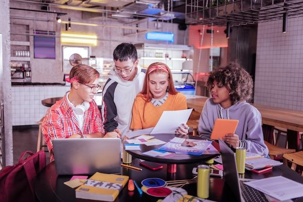 Время учиться. сосредоточенная международная девушка держит планшет в левой руке и смотрит на тетрадку своего друга