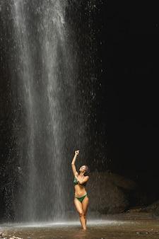 수영할 시간입니다. 폭포 아래 서서 그녀의 몸을 씻는 긍정적인 기뻐하는 갈색 머리 여성, 이국적인 장소