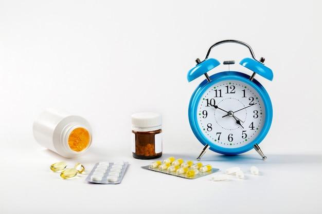 약을 먹을 시간입니다. 흰 벽의 알람 시계는 약물 복용 시간과 그 옆에 의료 약을 보여줍니다.