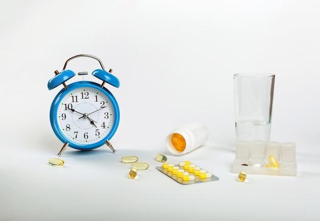 Пора принимать таблетки. будильник показывает время приема лекарств, а рядом - лечебные таблетки.