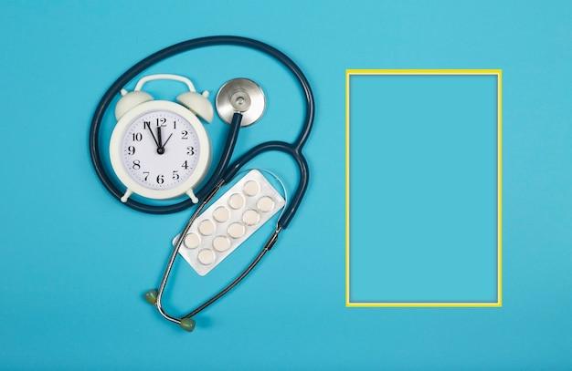 Пора принимать таблетки. таблетки, стетоскоп и будильник. вид сверху.