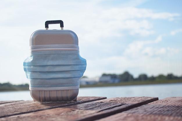 旅行の時間です。パンデミックcovid-19コロナウイルス中の安全な休息の概念。ビーチでの医療用マスク付き旅行用スーツケース