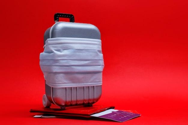 여행 할 시간입니다. 유행성 covid-19 코로나 바이러스 동안 비행 취소 및 안전한 휴식 개념. 의료용 마스크가있는 여행용 가방과 여권이있는 비행기 표.