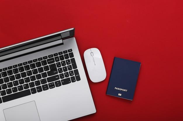 旅行する時間。赤い背景にパスポート付きのラップトップ。上面図。
