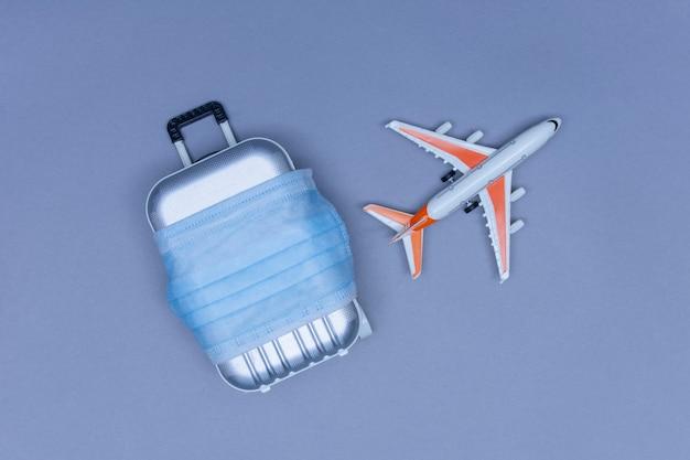 Пора путешествовать. концепция безопасного отдыха во время пандемии коронавируса covid-19. чемодан для путешествий с медицинской маской и самолетом.