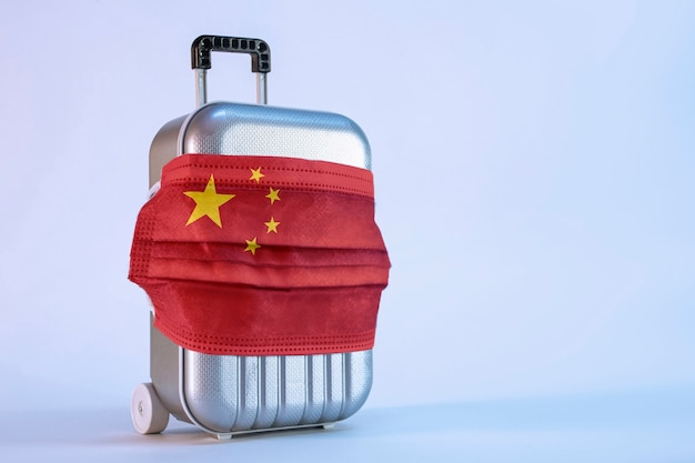 Пора путешествовать. концепция безопасного отдыха во время пандемии коронавируса covid-19. чемодан для путешествий с медицинской маской и флагом китая.