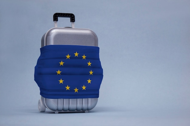 Пора путешествовать. концепция безопасного отдыха во время пандемии коронавируса covid-19. чемодан для путешествий с медицинской маской и флагом евросоюза.