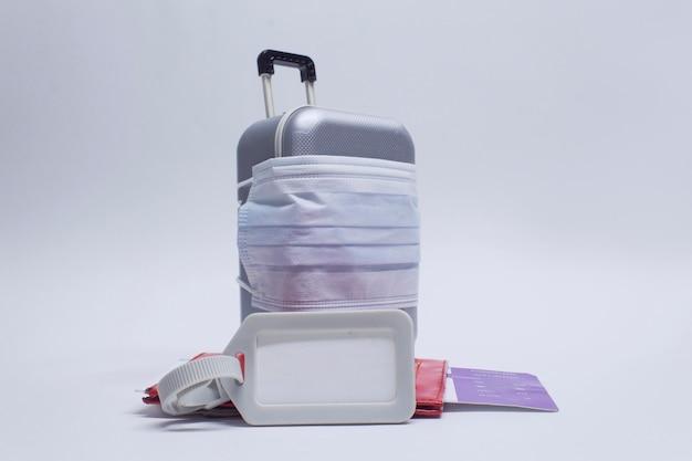 여행 할 시간입니다. 유행성 covid-19 코로나 바이러스 동안 안전한 휴식의 개념. 여권 및 태그 모형이있는 의료 마스크 및 비행기 티켓이있는 여행 가방.