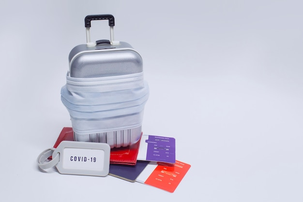 여행 할 시간입니다. 유행성 covid-19 코로나 바이러스 동안 안전한 휴식의 개념. 의료 마스크가있는 여행용 가방