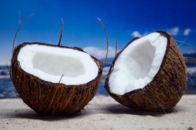 旅行の時間です。海を背景にビーチでココナッツの2つの半分。