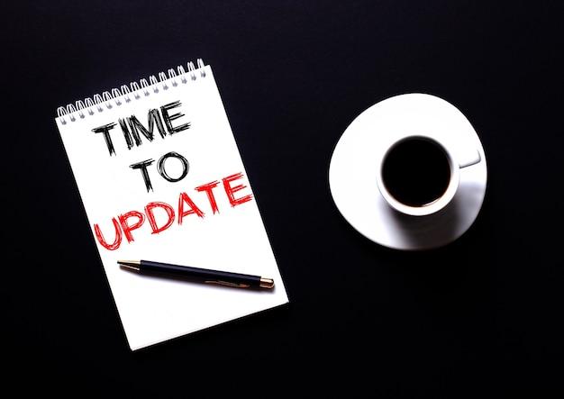 Время обновления написано в белой записной книжке красным шрифтом рядом с белой чашкой кофе на черном столе. мотивационная концепция
