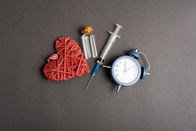 予防接種の時間、時計のワクチンと心臓の写真