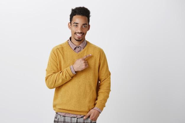 Пора посещать новые места. портрет очаровательного молодого темнокожего парня со стрижкой в стиле афро, вежливо улыбающегося и указывающего пальцем на верхний правый угол, улыбаясь, продвигая пространство для копирования