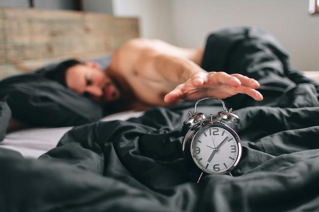 일어날 시간이야. 침대에서 피곤한 남자는 행복하지 않습니다. 작업 시간을 확인하는 동안 알람 시계를 들고 성숙한 남자
