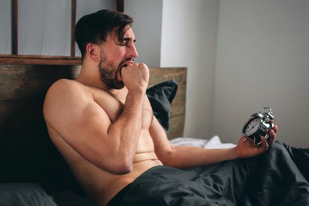 Время просыпаться. усталый мужчина в постели не рад. зрелый парень держит будильник во время проверки времени на работу