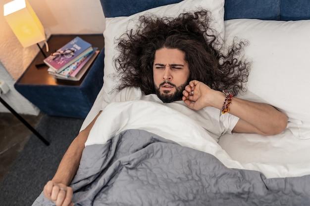 起きる時間。朝起きようとしている眠そうな若い男のトップ ビュー