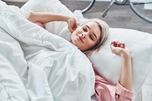 起きる時間!目を閉じて、自宅のベッドに横たわっている間ストレッチを維持する魅力的な若い女性の上面図 Premium写真