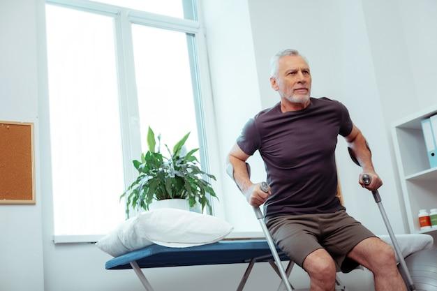 歩く時間。起き上がる準備ができている間、医療ベッドに座っている素敵な格好良い男