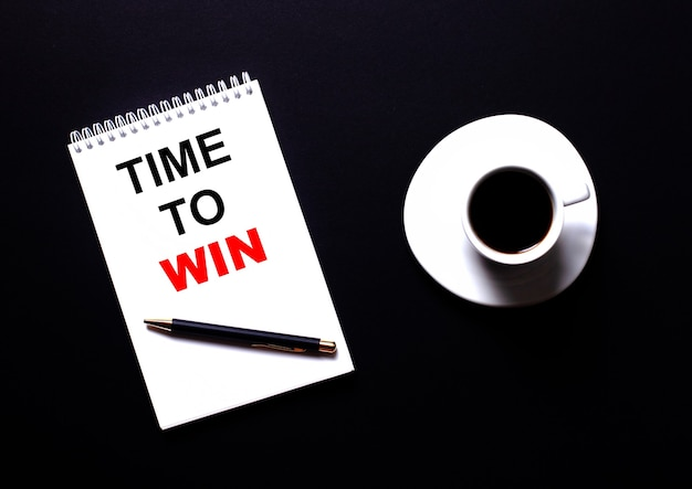 Time to win은 검은 색 탁자 위의 커피 한 잔 근처에 빨간색 활자체의 흰색 공책에 적혀 있습니다. 동기 부여 개념