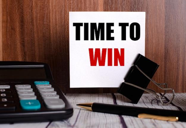 승리 할 시간은 계산기와 펜 옆의 나무 벽에있는 흰색 카드에 적혀 있습니다.