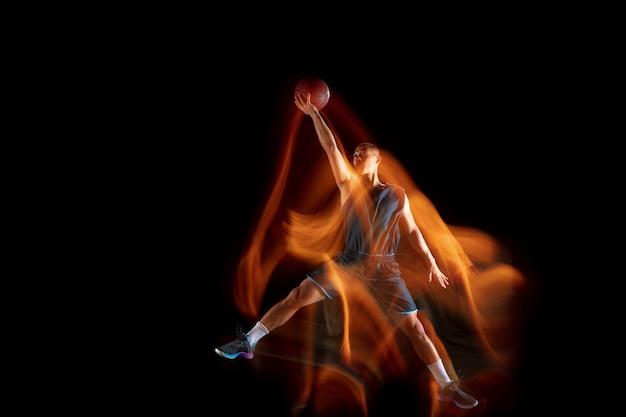 Время побеждать. молодой восточноазиатский баскетболист в действии и движении, прыгающий в смешанном свете на темном фоне студии. понятие спорта, движения, энергии и динамичного, здорового образа жизни.