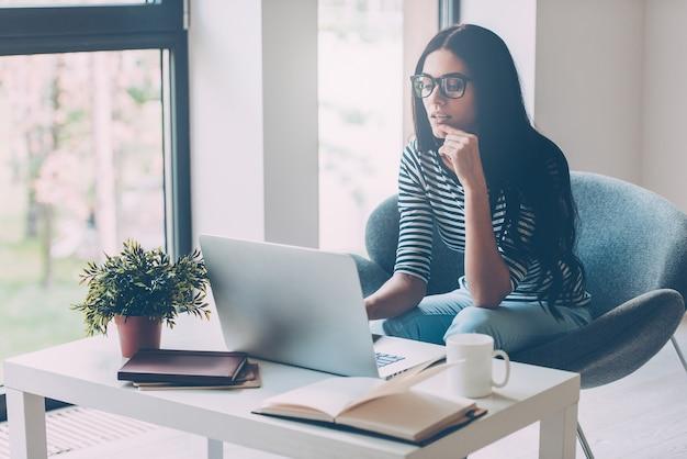 일할 시간. 작업장에 앉아 노트북 작업을 하는 자신감 있는 젊은 미녀