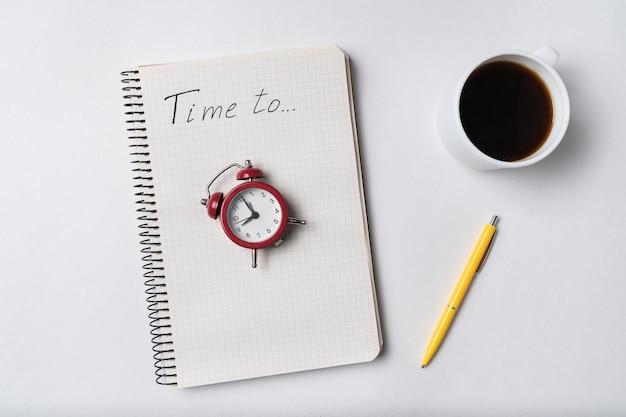 Записная книжка с надписью time to. блокнот и старинный будильник. планирование и кофе.