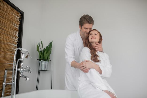 一緒に時間を。彼の妻を抱き締める白いバスローブを着た背の高い男