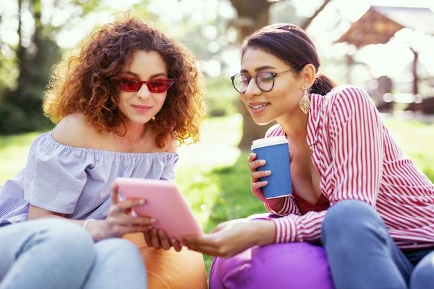 一緒に時間を。タブレットを持って友達と話している魅力的な幸せな女性