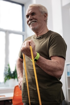 Time to train. delighted cheerful man standing in the exercise room while training with a rubber band