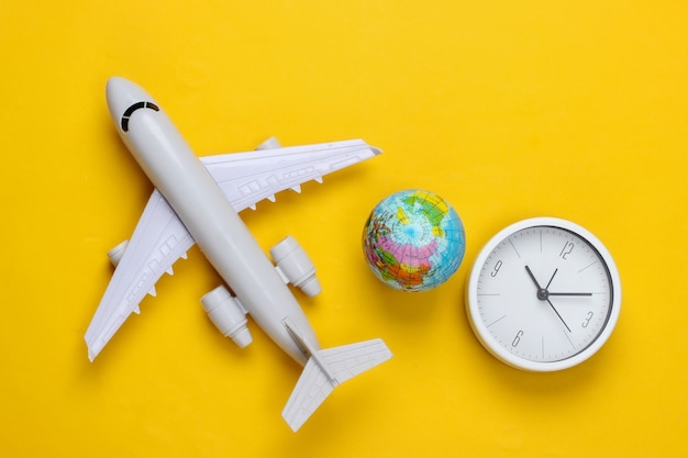 Time to travel. aircraft figurine, globe and clock on a yellow surface. top view