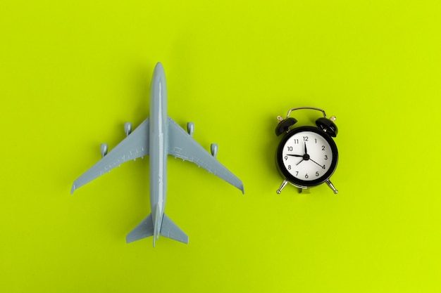 Time to travel concept. plastic plane jet toy passenger with alarm clock