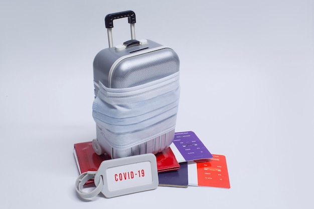 Time to travel. the concept of safe rest during a pandemic covid-19 coronavirus. suitcase for travel with a medical mask and plane tickets with a passport.