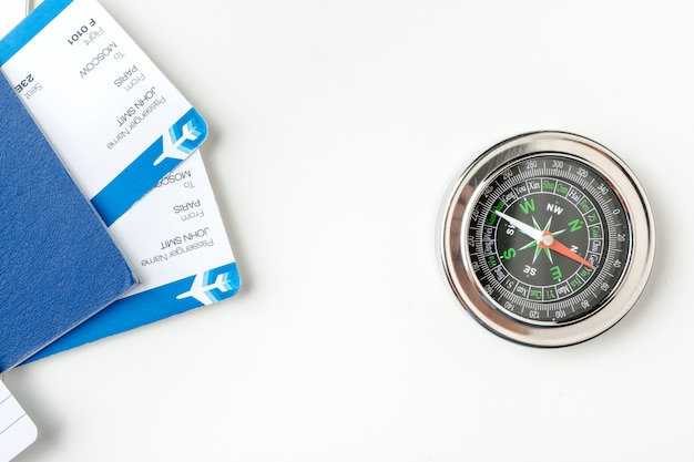 Time to travel. idea for tourism with flight tickets and compass on white