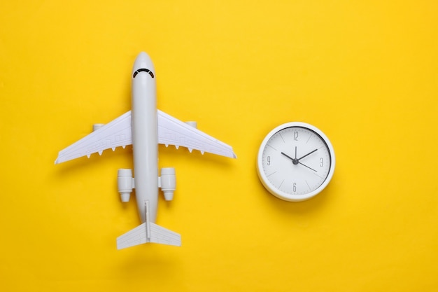 Time to travel. plane figurine and clock on a yellow surface. top view