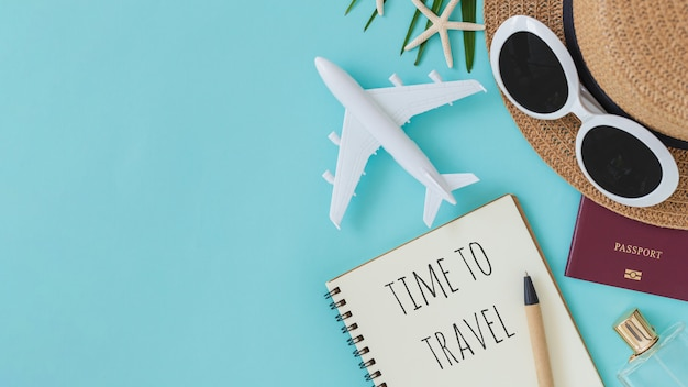 Time to travel quote in notebook with hat and airplane