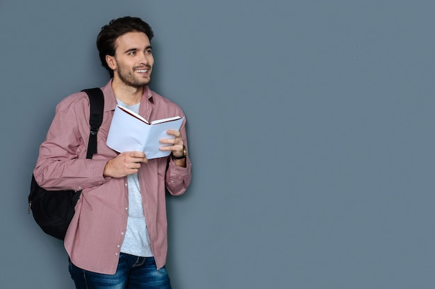 Time for travelling. cheerful handsome male tourist smiling and reading a tour guide while planning his trip
