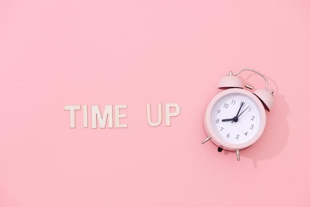 분홍색 배경에 그림자와 라이트 핑크 레트로 알람 시계와 함께 시간을 텍스트.