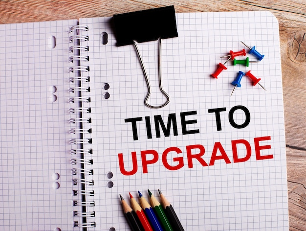 Time to upgrade is written in a notebook near multi-colored pencils and buttons on a wooden wall.