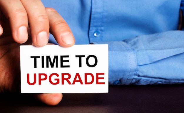 Time to upgrade is written on a white business card in a man's hand
