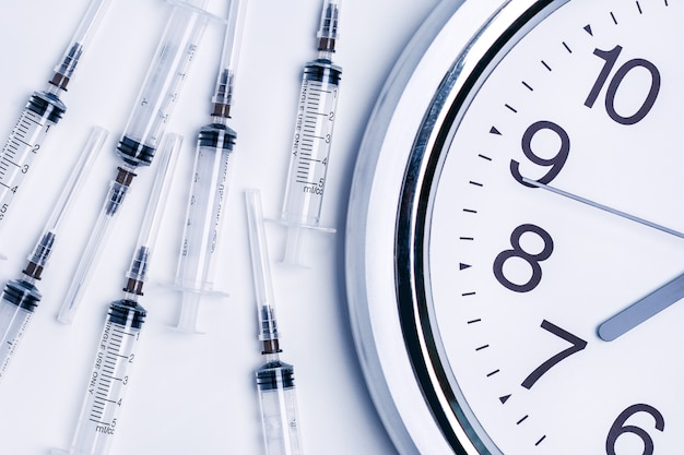 Time to vaccinate concept. syringes of vaccine and alarm clock