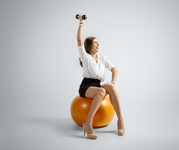 Time for weight loss. woman in office clothes training with weights on grey background