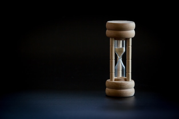 The time with hourglass on black color background
