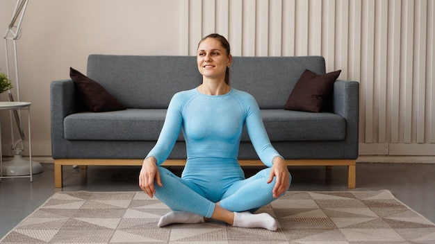 Time for yoga. attractive young woman exercising and sitting in yoga position while resting at home