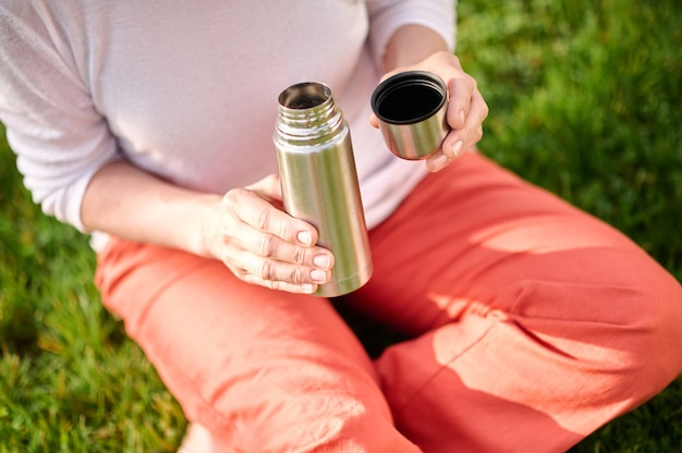 Time for yourself. female hands holding open small thermos with drink outdoors on sunny day, no face