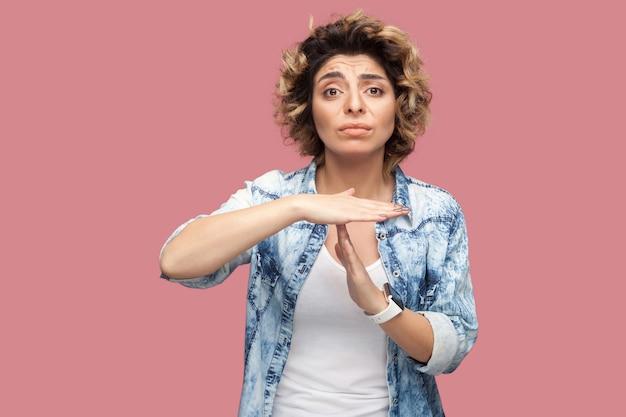 タイムアウト。私にはもっと時間が必要です。 tジェスチャーサインで立ってカメラを見てカジュアルな青いシャツの巻き毛の若い女性を喜ばせる心配の肖像画。スタジオショット、ピンクの背景に分離