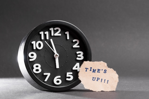 Times up blue text on torn paper near the black clock against black backdrop