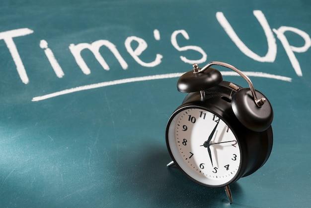 검은 알람 시계와 함께 녹색 칠판에 메시지를 시간